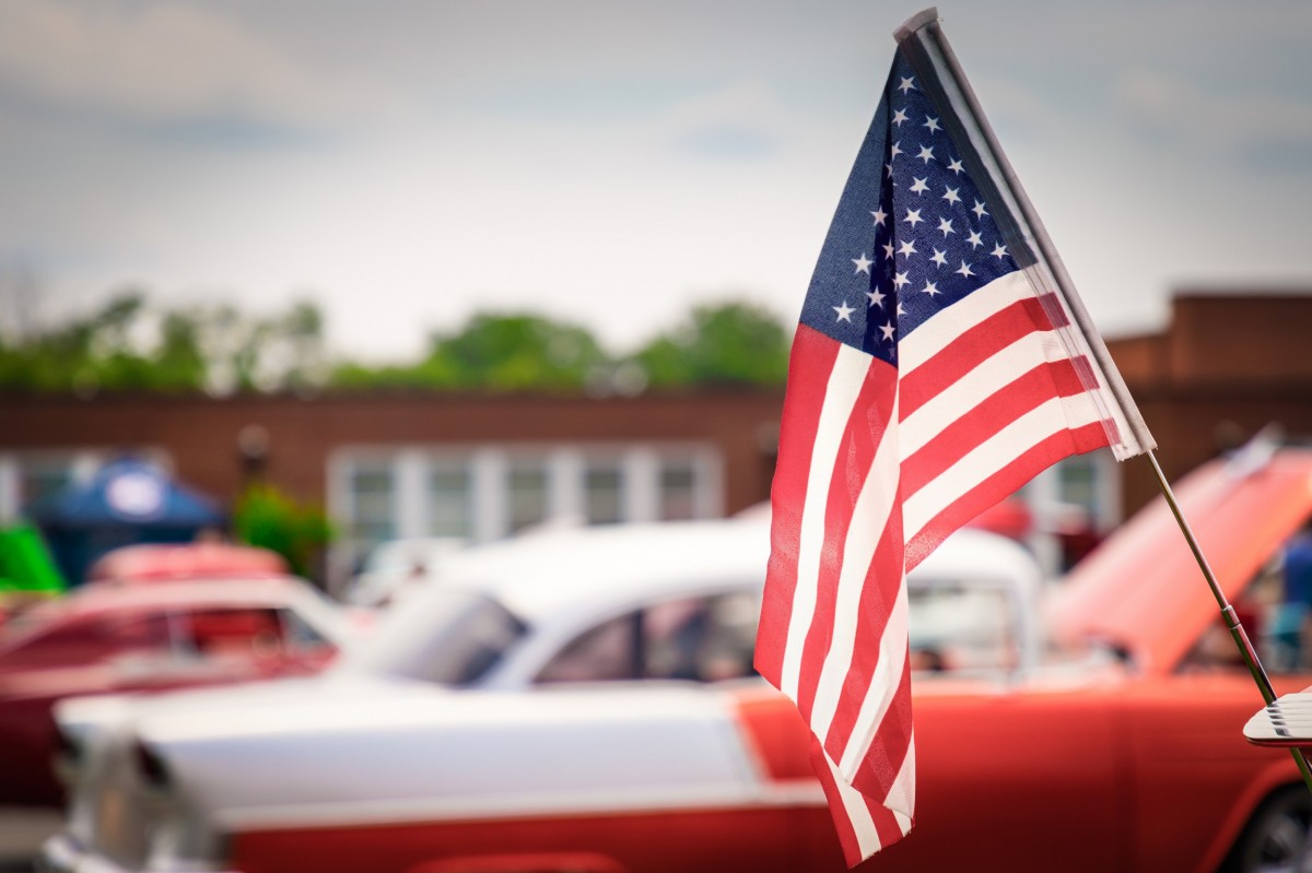 classic car in the background of a flag